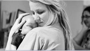 Sygeplejersken holder en døende nyfødt baby i sine arme. Det som hun skriver på