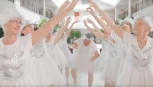 Ni 82-årige kvinder klædt i hvidt danser og synger. Se på bedstemoren i midten!