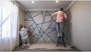 De dækker dele af væggen med selvklæbende tape. I vil blive begejstret, når I se
