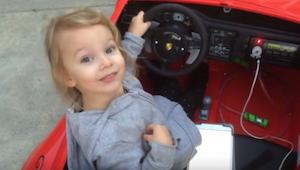 Den søde, lille 5-årige pige sætter sig ind i sin batteridrevne bil.  Efter et ø
