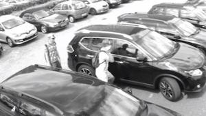 Manden kigger ind i bilen, og det ser ud som om han er ved at stjæle den. Den vi