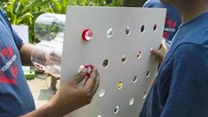 Man monterer overskårne flasker i et stykke karton, som derefter sættes fast i v