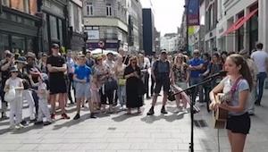 Den 12-årige begynder at synge og spille guitar på en gade i Dublin. Hendes tale