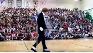 Den unge teenager går ud på midten af gulvet i gymnastiksalen, og så snart musik