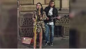 En pige klædt i en flirtende kjole og høje hæle nærmer sig en gademusiker, og sp