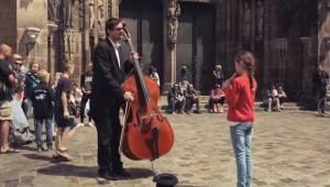 Den lille pige spiller fløjte til cellisten, et øjeblik senere bliver alle omrin