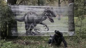 Se kunstneren lave graffiti på et stykke folie, som er spændt ud mellem to træer