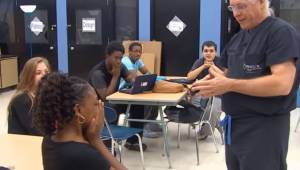 Lægen kommer ind i klassen og går hen til gymnasieeleven; da han fortæller hende