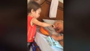 Den lille dreng hjælper son bedstefar med at indtage føde; det er et øjebliksbil