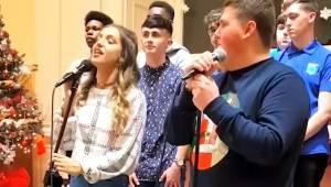 To teenagere forbereder sig til at optræde i en duet; - læg mærke til drengens r