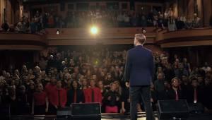 Sangeren står foran et kor med 200 unge mennesker. Hør denne fremragende version